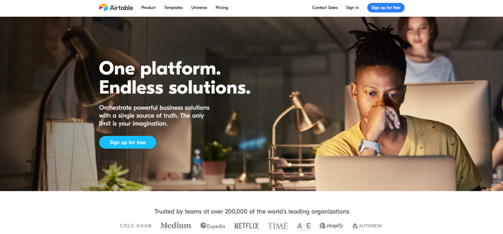 Airtable homepage, featuring one platform and endless solutions with a man working on a laptop